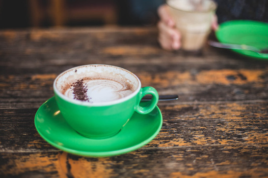 A green cup of a coffee on a wooden table